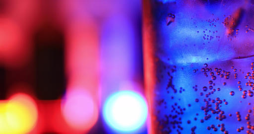 A bottle glass of soda water with neon light closeup Live Action