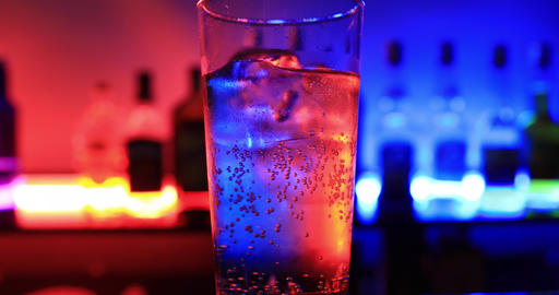 A bottle glass of soda water with neon light Live Action