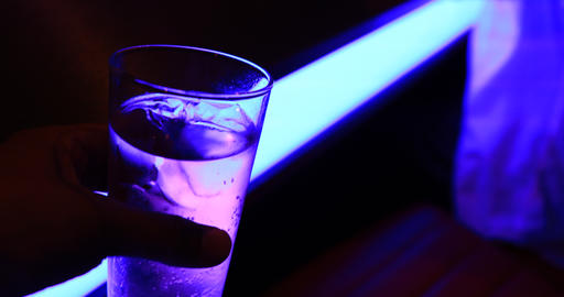 A bottle glass of soda water with neon light closeup handheld Live Action