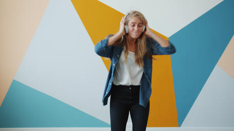 Cute young lady dancing on colorful background wearing wireless headphones Live Action