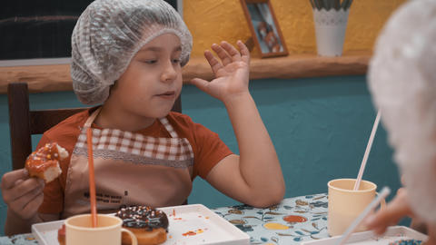 Boy eating tasty doughnut after culinary master class Live Action