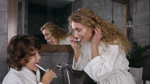 Attractive young woman with long curly hair in white bathrobe brushing teeth Live Action