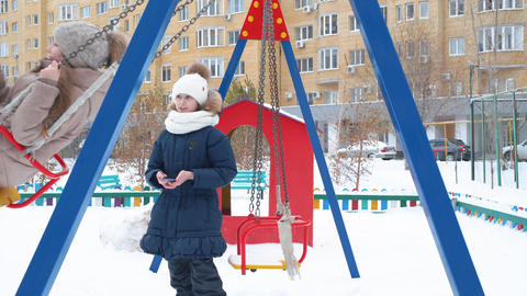 Teenager girl swinging on snowy playground at holiday vacations in winter city Live Action