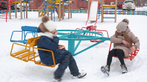 School girls turning on carousel swing on snowy playground at winter vacations Live Action