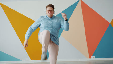 Playful young man dancing on colorful background wearing headphones enjoying Live Action