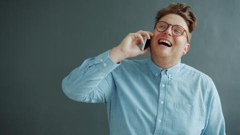 Joyful guy talking on mobile phone laughing enjoying communication on gray Live Action