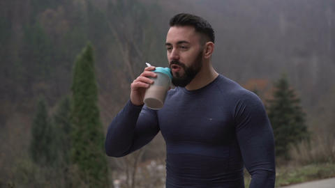 Healthy Strong Man with Beard Drinking Protein Drink outdoors with misty forest Live Action