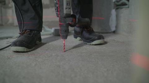 Worker put a plastic dowel in the concrete floor. Worker drills concrete floor Live Action