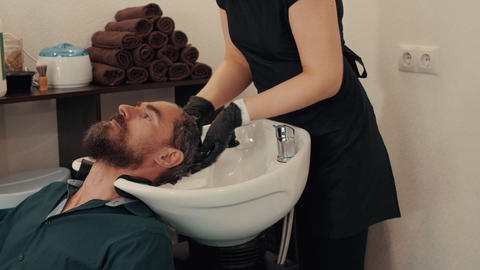 Hairstylist washing male hair with shampoo in barber salon. Hairdresser hand Live Action
