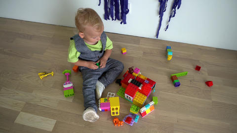 Baby boy plays play assembly constructor parts on wooden floor. Gimbal motion Live Action