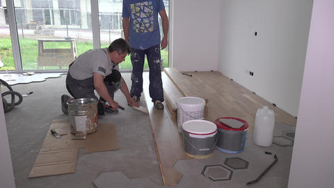 Workers with dirty clothes lay parquet floor boards in living room Live Action