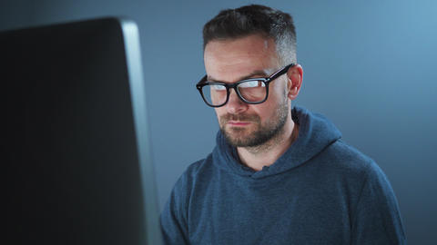 Bearded male hacker in hoodie and glasses working on a computer in a dark office Live Action