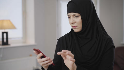 Young Muslim woman in traditional hijab looking at smartphone screen and making Live Action