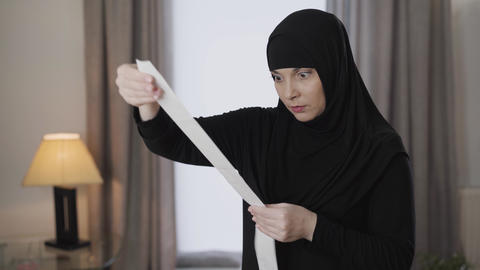 Young stressed Muslim woman in traditional hijab raising up bill and looking at Live Action
