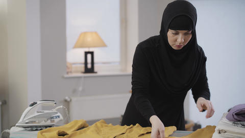 Middle shot of beautiful Muslim woman in traditional clothes ironing yellow Live Action
