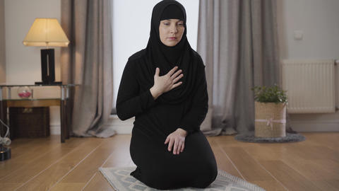 Portrait of young Muslim woman in black traditional hijab bowing down and Live Action
