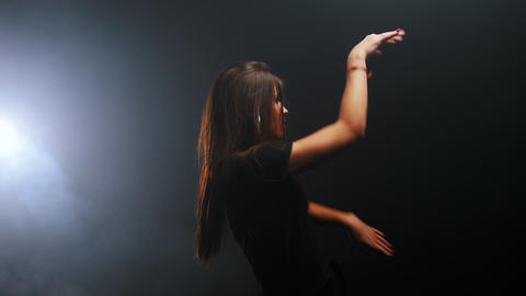 Young woman with long dark hair dancing in the dark Live Action