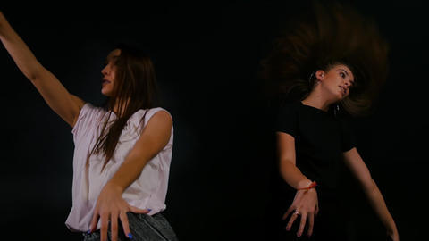 Two young women freestyle dancing in dark indoors Live Action