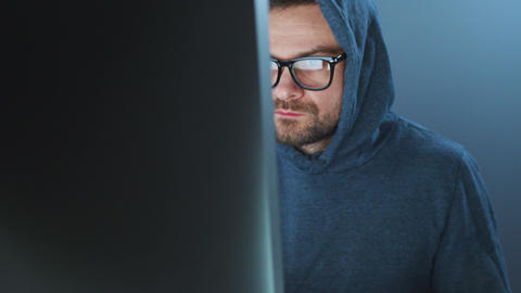 Male hacker in the hood and glasses working on a computer in a dark office room Live Action