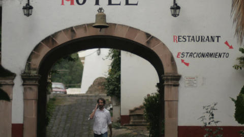 A thin, fit man walks under a generic hotel archway talking on a phone Footage