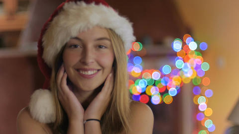 A beautiful young woman smiles and looks at the camera in a Christmas hat in slo Footage