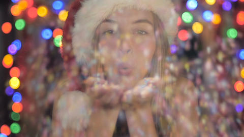 A cute, attractive woman in a Santa hat blowing confetti in slow mo with colored Footage