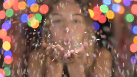 A happy attractive woman blows confetti at the camera in slow mo with colored Footage