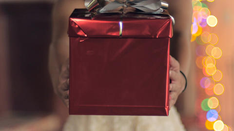 A young woman presents a red wrapped gift box with a silver bow towards the came Footage