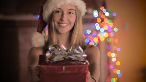 A beautiful young woman wearing a Santa hat gives a red wrapped wrapped gift Footage