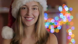An pretty young woman winking, laughing and wearing a Santa hat in front of colo Footage