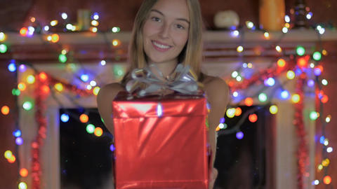 A beautiful young lady gives a Christmas present towards the camera with colored Footage