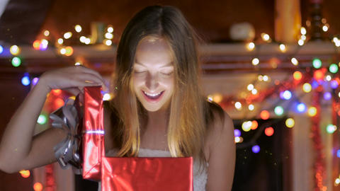 A pretty blond haired woman opens a gift with colored lights behind her Footage