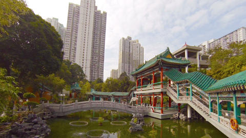 Highrise Buildings Overshadow Buddhist Temple Garden in Southeast Asia Footage