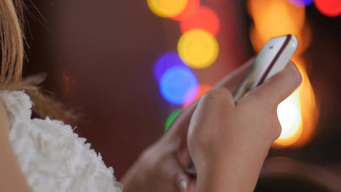Close up of a woman using her smart phone by the fire during the holidays with C Footage