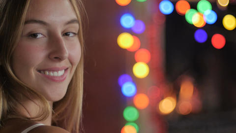 A young woman on her phone turns and smiles at the camera during the holidays wi Footage