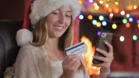 A young attractive woman wearing a Santa hat completes her online order and says Footage