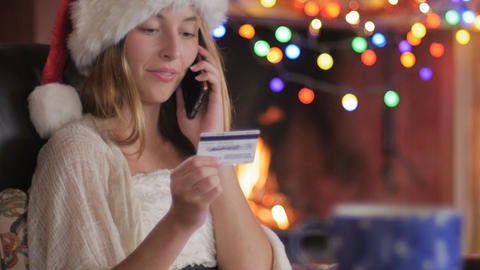 A beautiful woman wearing a Santa hat calls in her order with a credit card Footage