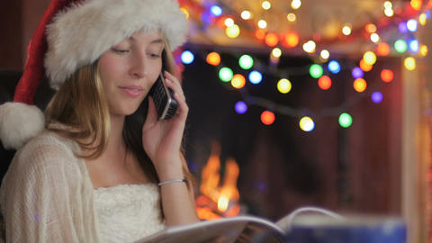 A young attractive woman wearing a red Santa hat places a phone order with a Footage