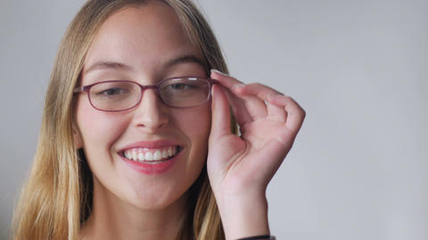 An attractive young woman with long blond hair tries on eyeglasses and smiles ag Footage