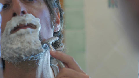An attractive man uses a single blade safety razor to shave his beard - handheld Footage