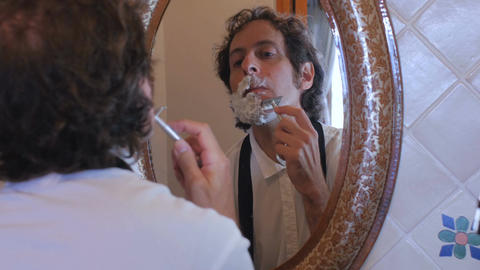 A business man shaving and getting ready for work checks his watch and runs out Footage