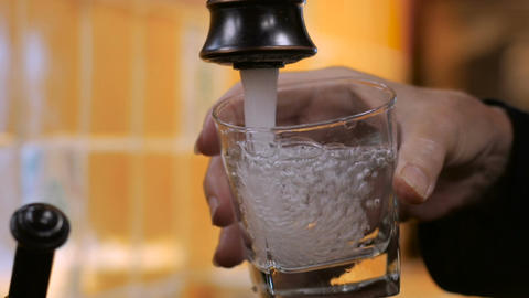 Close up of a man filling a glass with clean drinking water from a faucet and th Footage