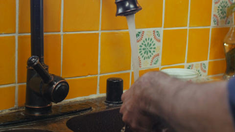 A man washes a knife with a sponge and soap under running water - fast shutter s Footage