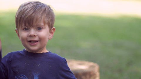 Little blond 3 year old boy looking at camera waving, smiling, and playing with Footage