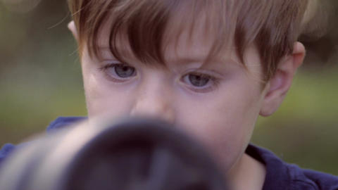 Small little blond boy with big blue eyes playing with the wheels from a toy car Footage