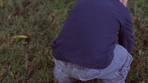 Little blond boy walking on grass outside with cute clothes as camera follows hi Footage