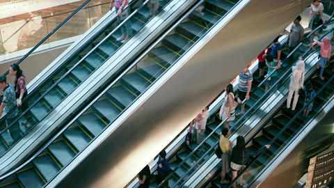 People move on escalator staircases inside of shopping mall Footage