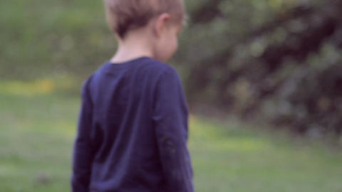Cute little blond boy in blue clothes walks and plays on green grass turns to lo Footage
