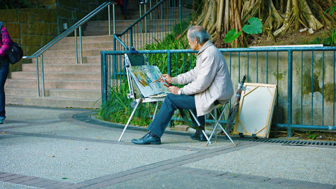 Street artist in front of his easel. painting with watercolors in Hong Kong Footage