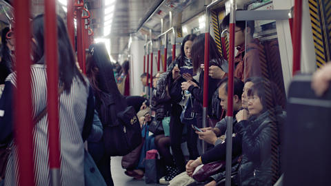 Many commuters. crowded onto a subway car in Hong Kong. at night Footage